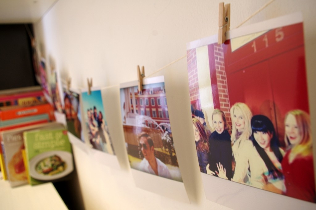 Polaroid style photos displayed on string with micro pegs.